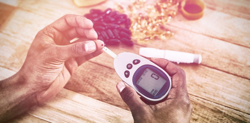 Diabetic woman testing blood sugar with glucometer next to supplements