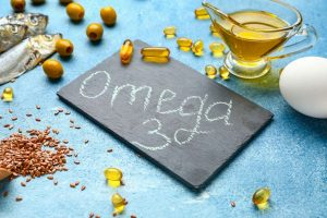 Fish, oils, fish oil pills and foods with high omega-3 content on blue background